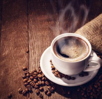 Filiżanka aromatycznej kawy na stole z ciemnego drewna, otoczona rozsypanymi ziarnami palonej kawy.