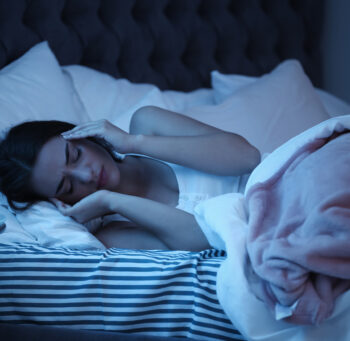 Kobieta leżąca w ciemności w łóżku i trzymająca się za bolącą głowę.